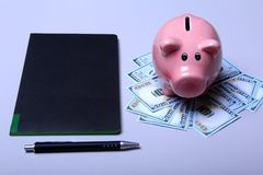 Piggy bank style money box on background with money american hundred dollar bills.  Stock Image