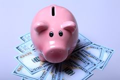 Piggy bank style money box on background with money american hundred dollar bills.  Stock Photo