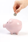 Piggy bank style money box with one euro falling into slot on white background Royalty Free Stock Photos