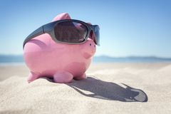 Piggy bank with sunglasses on the beach in Summer royalty free stock image