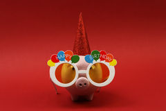 Piggy bank with sunglasses Happy birthday, party hat on red background Royalty Free Stock Photos