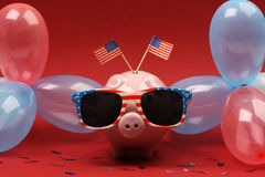 Piggy bank with sunglasses with USA flag and blue, red and white party balloons and two small USA flags on red background. 