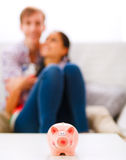 Piggy bank on table and couple in background Stock Photography