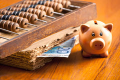 Piggy bank on a table by the old book, abacus and 20 euro bankno Stock Photography