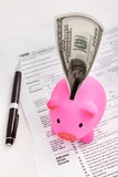 Piggy bank and tax forms Stock Photography