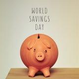Piggy bank and text world savings day Stock Photos
