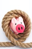 Piggy bank tied by rope Royalty Free Stock Images