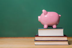 Piggy bank on top of books with chalkboard Royalty Free Stock Images