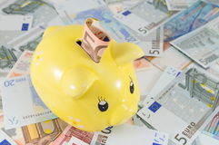 Piggy bank on top euro bills. Piggy bank on top of euro bills Royalty Free Stock Images