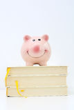 Piggy bank on top of pile of books suggesting saving for college concept Stock Photo