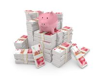 Piggy bank on top of pile of yuans Stock Image