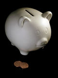 Piggy bank and two cents. A white piggy bank and two cents Royalty Free Stock Photos