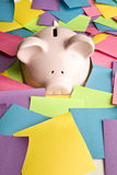 Piggy bank up to its nose in post it notes Stock Photos