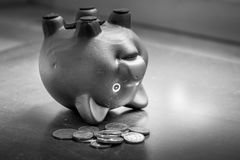 Piggy bank upside down on table, financial problems and debt concept. Royalty Free Stock Images