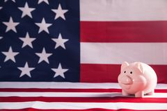 Piggy bank on USA flag background royalty free stock images