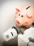Piggy bank and the valve on the radiator for energy savings Royalty Free Stock Images