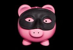Piggy bank wearing black masquerade mask Royalty Free Stock Image