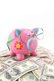 Piggy bank wearing glasses. Shot over one hundred and fifty US dollars note Stock Photo