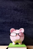 Piggy bank wearing glasses with blackboard, college saving fund or graduation concept Stock Image