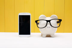 Piggy bank wearing glasses with cellphone Stock Images