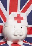 Piggy bank wearing nurse hat. On british flag stock photos