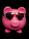 Piggy bank wearing union jack heart sunglasses Royalty Free Stock Photos