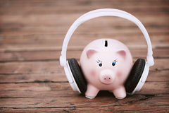 Piggy Bank with White Headphones at the Wooden Table Royalty Free Stock Images