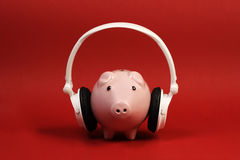 Piggy bank with white headset standing on red background Royalty Free Stock Photography