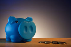 Piggy bank on a wooden base black background Royalty Free Stock Images