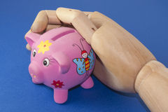 Piggy bank in a wooden hand Royalty Free Stock Image