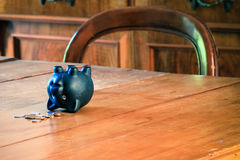 Piggy bank on wooden table. Black piggy bank and cash coins on table Stock Photos