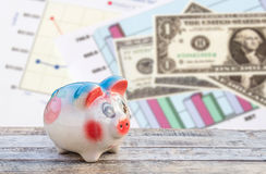 Piggy bank on wooden table over dollars and financial paper grap Royalty Free Stock Images