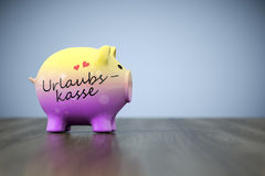Piggy bank with the word holiday fund in german language Stock Image