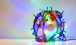 Piggy bank wrapped in Christmas string lights. isolated Royalty Free Stock Photos