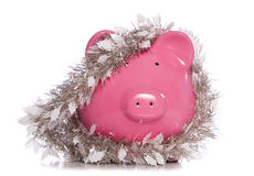 Piggy bank wrapped in Christmas tinsel Stock Images