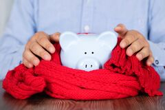 Piggy bank wrapped in scarf in front of man