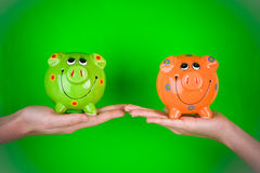 Piggy banks. A pair of hands holding ceramic piggy banks Royalty Free Stock Photos