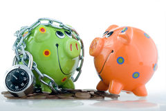 Piggy banks. Two painted piggy banks with one in chains Royalty Free Stock Image