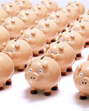 Piggy Banks Bank Business Saving. Many piggybanks lined up in rows on a white surface Royalty Free Stock Images