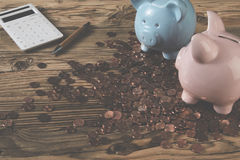 Piggy banks with calculator and pen among coins. Two piggy banks with calculator and pen on wooden table among coins Stock Photo