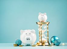 Piggy banks with hourglass wrapped in lights royalty free stock photography
