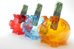 Piggy banks with hundred euro bills Royalty Free Stock Image