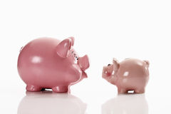 Piggy banks, opposing each other Stock Image