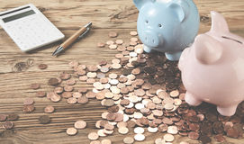 Piggy banks with pen and calculator among coins. Two piggy banks with calculator and pen on wooden table among saved coins Royalty Free Stock Images