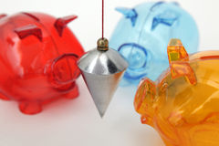 Piggy banks with plumb. Three colorful piggy banks with metal plumb on white background Royalty Free Stock Photos