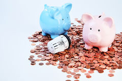 Piggy banks and radiator valve among coins. Two piggy banks and thermostatic radiator valve on heap of saved coins Royalty Free Stock Image