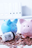 Piggy banks with radiator valve among coins. Two piggy banks with thermostatic radiator valve among saved coins Royalty Free Stock Image