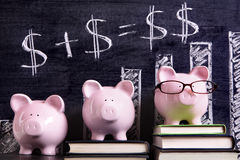 Piggy Banks with savings or retirement growth plan. Three pink piggy banks standing on books next to a blackboard with simple money math and bar chart.  Sharp Stock Photos
