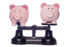 Piggy banks on scales Royalty Free Stock Photo
