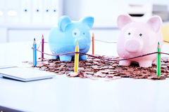 Piggy banks standing on coins. Two piggy banks standing on coins behind colored pencils fence Royalty Free Stock Images